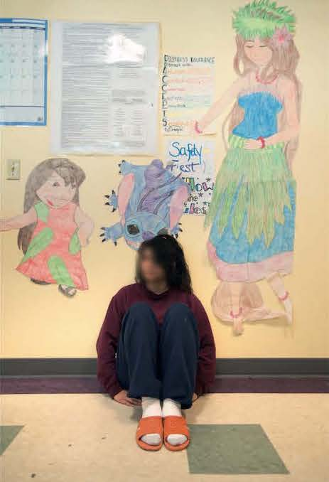 girl sits on the floor against wall